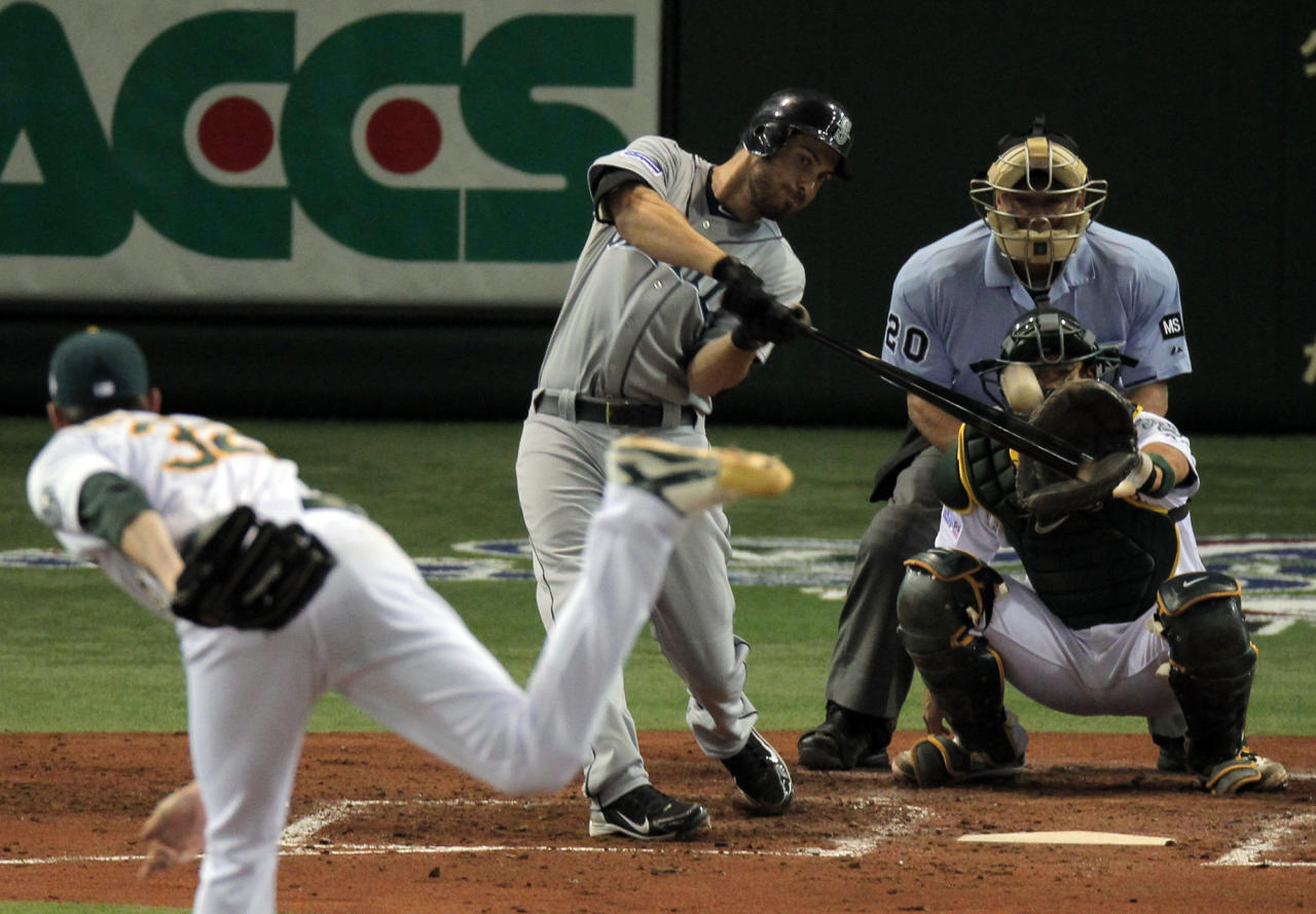 Seattle Mariners' Dustin Ackley hits a solo shot against Oakland Athletics starter Brandon McCarthy as Oakland Athletics catcher Kurt Suzuki looks on in the fourth inning of their American League season opening MLB baseball game at Tokyo Dome in Tokyo, Wednesday, March 28, 2012. (AP Photo/Itsuo Inouye)