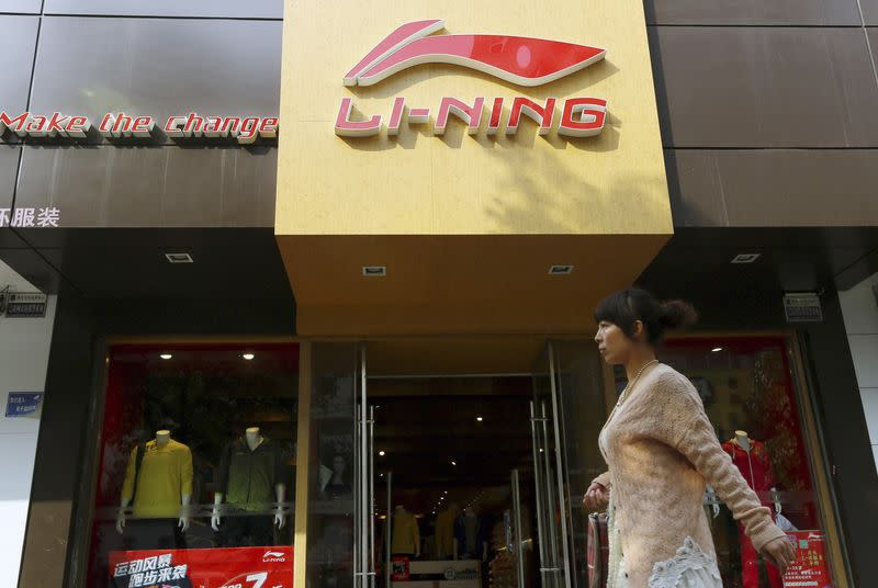 File picture of a woman walking past a Li Ning sportswear store in Huaibei