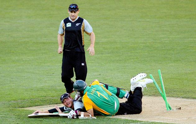 Martin Guptill of New Zealand runs out Hashim Alma of South Africa while teammate Nathan McCullum looks on during the first International Twenty20 match between New Zealand and South Africa at Westpac Stadium on February 17, 2012 in Wellington, New Zealand.  (Photo by Hagen Hopkins/Getty Images)
