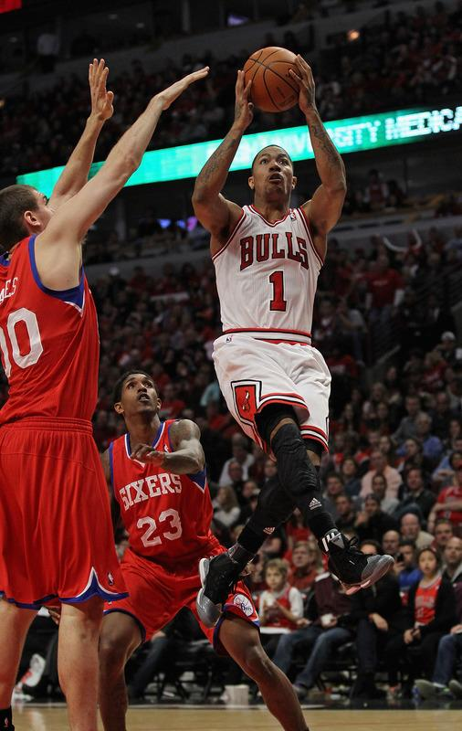 CHICAGO, IL - APRIL 28: Derrick Rose #1 of the Chicago Bulls goes up for a shot against Louis Williams #23 and Spencer Hawes #00 of the Philadelphia 76ers in Game One of the Eastern Conference Quarterfinals during the 2012 NBA Playoffs at the United Center on April 28, 2012 in Chicago, Illinois. The Bulls defeated the 76ers 103-91. NOTE TO USER: User expressly acknowledges and agrees that, by downloading and or using this photograph, User is consenting to the terms and conditions of the Getty Images License Agreement. (Photo by Jonathan Daniel/Getty Images)