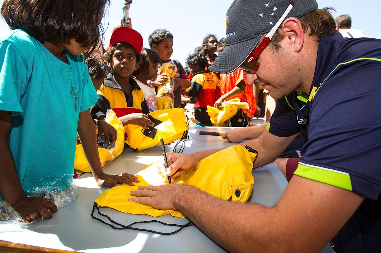 DARWIN, AUSTRALIA - AUGUST 10: Ryan Harris of the Australian cricket team signs autogrphs during a visit to Pirlangimpi of the Tiwi Islands on August 10, 2012 on the Tiwi Islands, Australia.  (Photo by Mark Nolan/Getty Images)