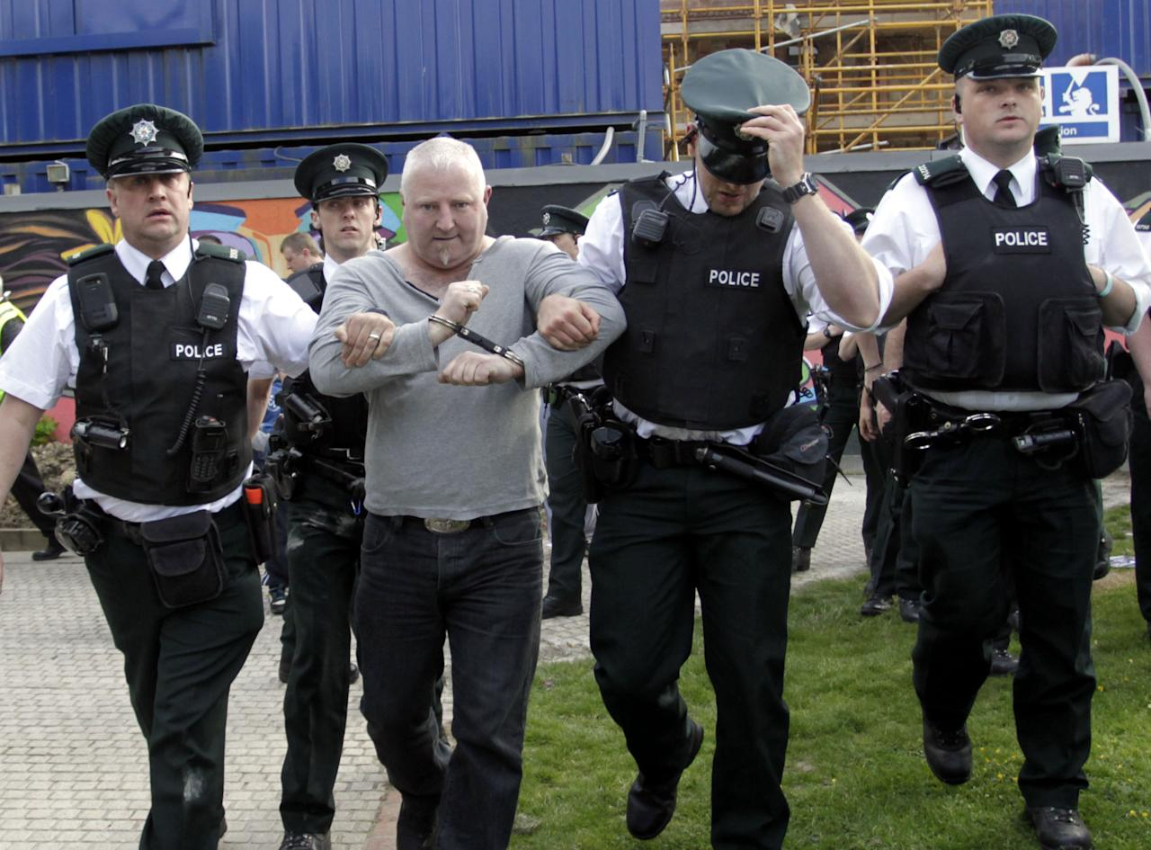 A Irish Republican protester is arrested by Police Service of Northern Ireland officers as the Olympic torch tried to pass in Londonderry, Monday, June 4, 2012. Republican protesters caused the Olympic torch to be rerouted Monday. (AP Photo/Peter Morrison)