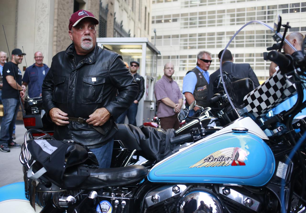 Singer Billy Joel gets off a motorcycle after riding from the Rescue 1 firehouse on West 43rd Street downtown to Ground Zero to honor the victims of the 9/11 attacks, outside the World Trade Center site in New York September 11, 2013. Bagpipes, bells and a reading of the names of the nearly 3,000 people killed when hijacked jetliners crashed into the World Trade Center, the Pentagon and a Pennsylvania field marked the 12th anniversary of the September 11 attacks in 2001. REUTERS/Shannon Stapleton (UNITED STATES - Tags: POLITICS ANNIVERSARY ENTERTAINMENT)