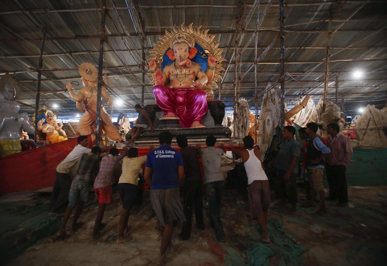 "Workers push a trolley with an idol of Hindu elephant god Ganesh, the deity of prosperity, as it is transported from a workshop to a place of worship in Mumbai September 3, 2013. The idols will be paraded through the streets in a procession during the Ganesh Chaturthi festival, accompanied by dancing and singing. They will then be immersed in a river or the sea symbolizing a ritual send-off of Ganesh's journey towards his abode in ""Kailash"", while taking away with him the misfortunes of all mankind. The festival will be celebrated on September 9. REUTERS/Danish Siddiqui (INDIA - Tags: SOCIETY RELIGION)"