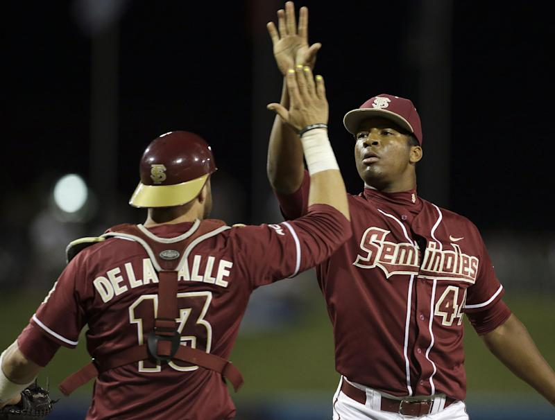 Florida State catcher Danny De La Calle (13) exchanges high-fives with pitcher Jameis Winston (44) after defeating Virginia 6-4 in the Atlantic Coast Conference college baseball tournament in Greensboro, N.C., Saturday, May 24, 2014