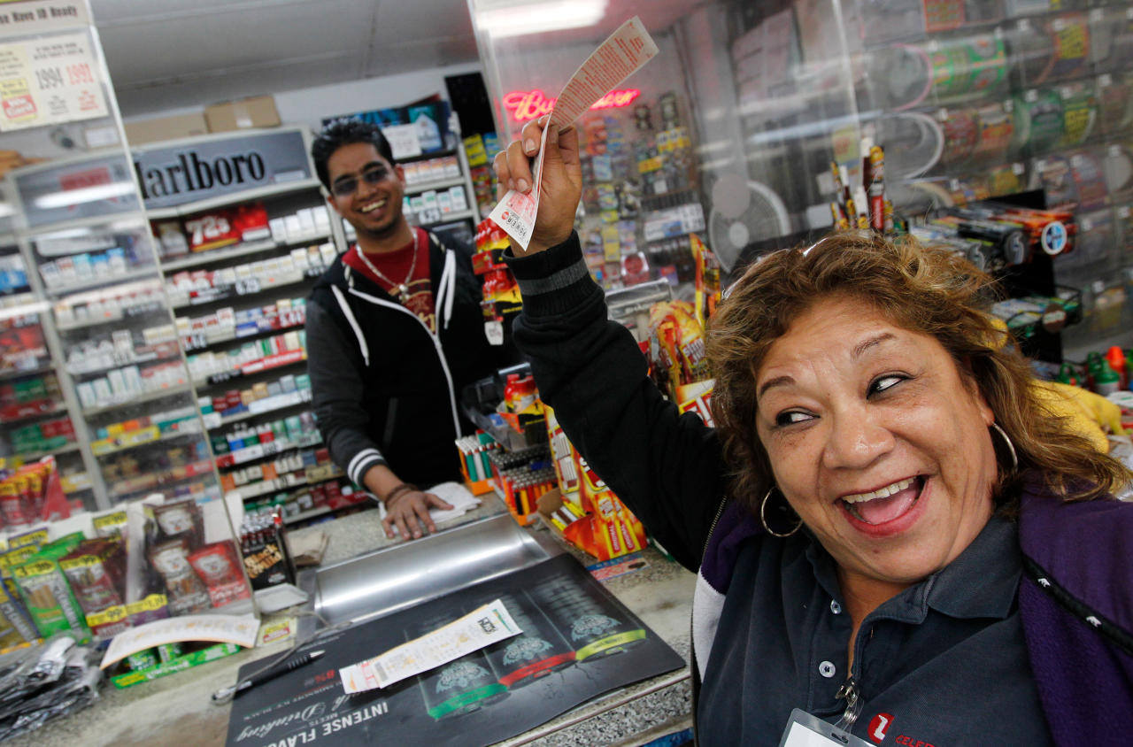 Raising her Power Ball ticket in the air Hortcina Martinez, who plays power ball weekly, shouts in excitement in hopes of winning jackpot from a ticket purchased at Oscar's Food Mart #1 on Tuesday, Nov. 27, 2012, in Houston. Wednesday's Powerball jackpot was raised to $500 million from $425 million. (AP Photo/Houston Chronicle, Mayra Beltran)