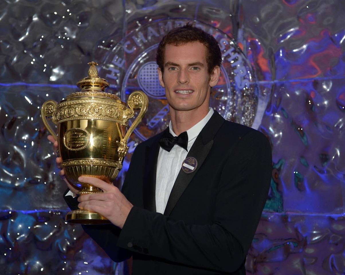 Andy Murray poses with the mens singles trophy during the Champions Ball at the Intercontinental Hotel, London.