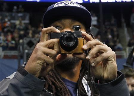 Seattle Seahawks cornerback Richard Sherman takes some pictures as he arrives for Media Day for Super Bowl XLVIII at the Prudential Center in Newark