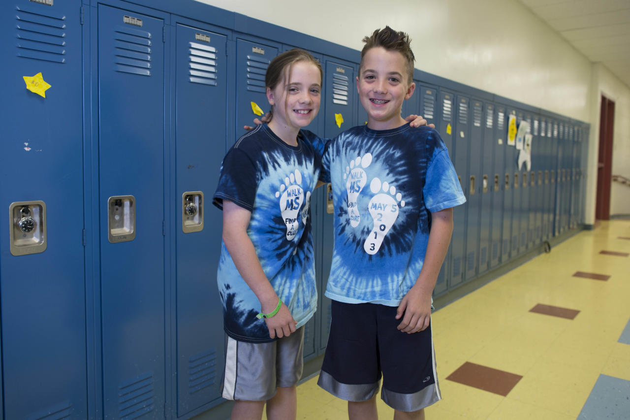 In this Thursday, June 6, 2013 photo, Maeve Holmberg, left, and her twin brother, Aidan, one of the twenty-four sets of twins from Highcrest Middle School in Wilmette, Ill., pose for a portrait at the school. The group is attempting to break a Guinness World record for the amount of twins in one grade which is currently 16 sets. (AP Photo/Scott Eisen)