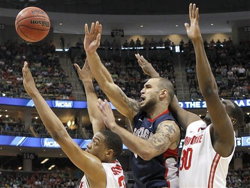 Gonzaga's Robert Sacre, center, tries to squeeze a shot between Ohio State's Evan Ravenel (30) and Lenzelle Smith, Jr., left in the first half of an East Regional NCAA tournament third-round college basketball game on Saturday, March 17, 2012 in Pittsburgh. (AP Photo/Keith Srakocic)