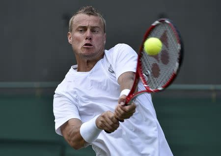 Lleyton Hewitt of Australia hits a return to Michal Przysiezny of Poland during their men's singles tennis match at the Wimbledon Tennis Championships, in London