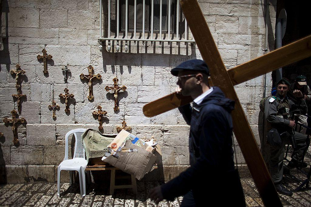 A Christian pilgrim carries a wooden crosses along the Via Dolorosa during Good Friday procession in Jerusalem, Israel.
