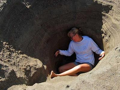 stuck in a hole in the sand digging dug dig debt