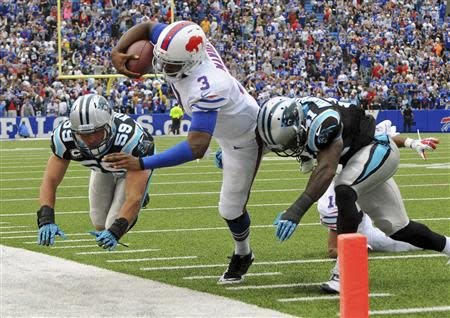 Buffalo Bills quarterback EJ Manuel is knocked out of bounds by Carolina Panthers cornerback Captain Munnerlyn and linebacker Luke Kuechly late in the fourth quarter of their NFL football game in Orchard Park