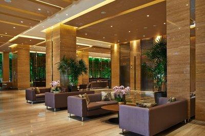 The expansive lobby is designed in warm tones framed against a screen of elegant bamboo