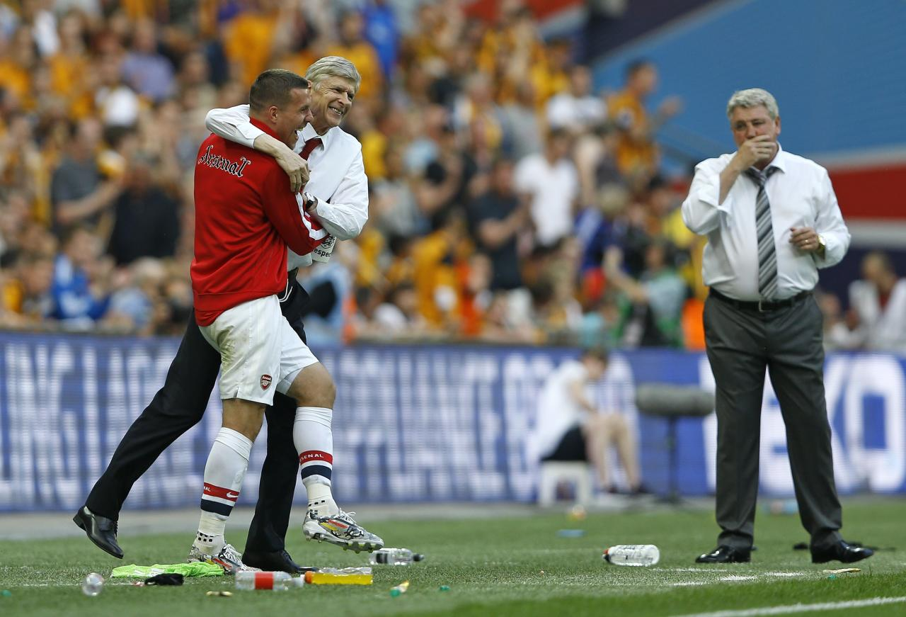 Arsenal's coach Arsene Wenger celebrates with Lukas Podolski as Hull coach Steve Bruce looks on after his team won the English FA Cup final soccer match between Arsenal and Hull City at Wembley Stadium in London, Saturday, May 17, 2014. Arsenal won 3-2 after extra-time. (AP Photo/Kirsty Wigglesworth)