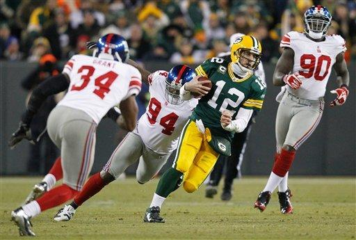 Green Bay Packers quarterback Aaron Rodgers (12) runs from New York Giants defenders Deon Grant (34), Mathias Kiwanuka (94) and Jason Pierre-Paul (90) during the first the second half of an NFL divisional playoff football game Sunday, Jan. 15, 2012, in Green Bay, Wis. (AP Photo/Jeffrey Phelps)