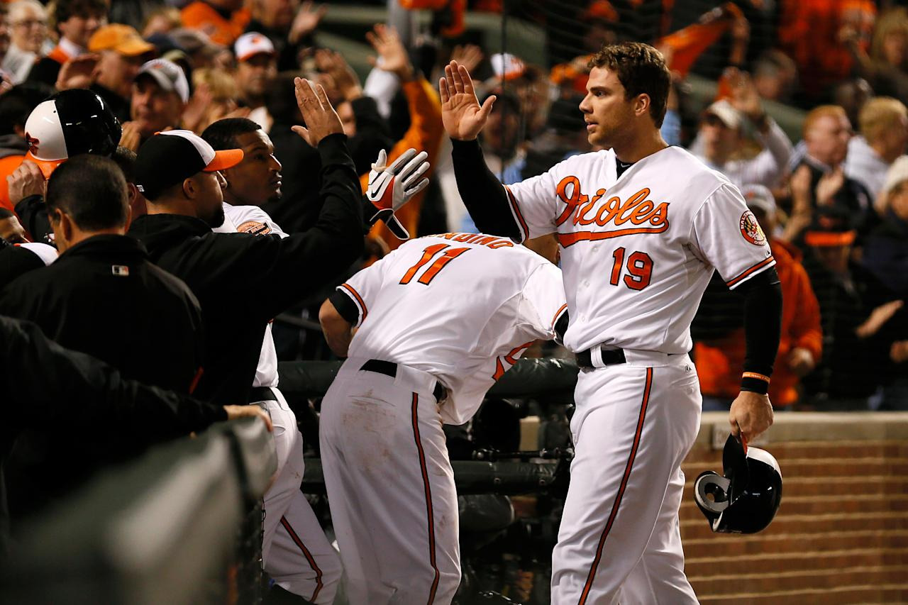 BALTIMORE, MD - OCTOBER 07:  Chris Davis #19 of the Baltimore Orioles celebrates with teammates after he scored on a 2-run single by Nate McLouth #9  in the bottom of the third inning against the New York Yankees during Game One of the American League Division Series at Oriole Park at Camden Yards on October 7, 2012 in Baltimore, Maryland.  (Photo by Rob Carr/Getty Images)