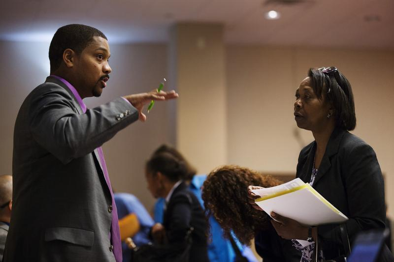 Woman stands with her paperwork as she speaks with a recruiter while attending a job fair in New York
