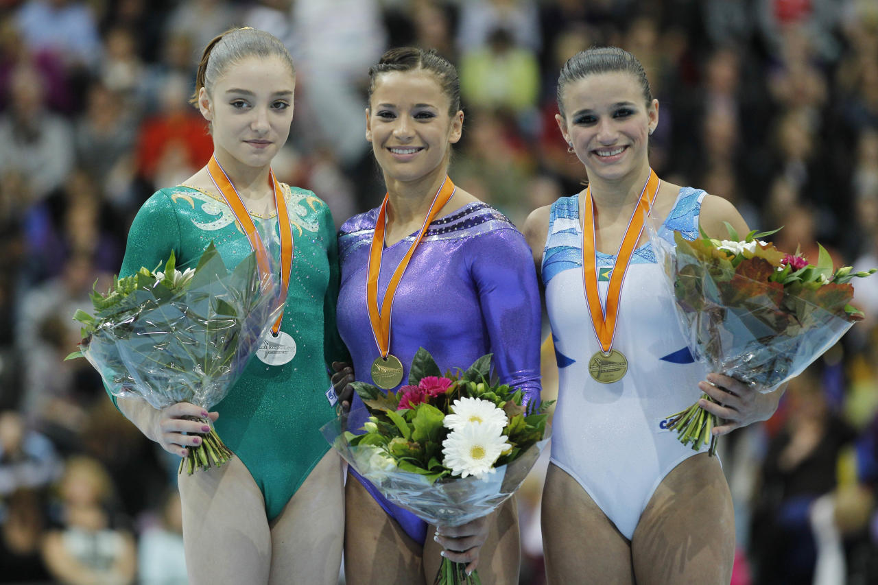 Aliya Mustafina of Russia, left, silver medal, Alicia Sacramone of the U.S., center, gold medal, and Jade Fernandes Barbosa of Brazil, right, bronze medal, are seen on the podium after the women's vault finalof the World Championships Gymnastics in Rotterdam, Netherlands, Saturday Oct. 23, 2010.