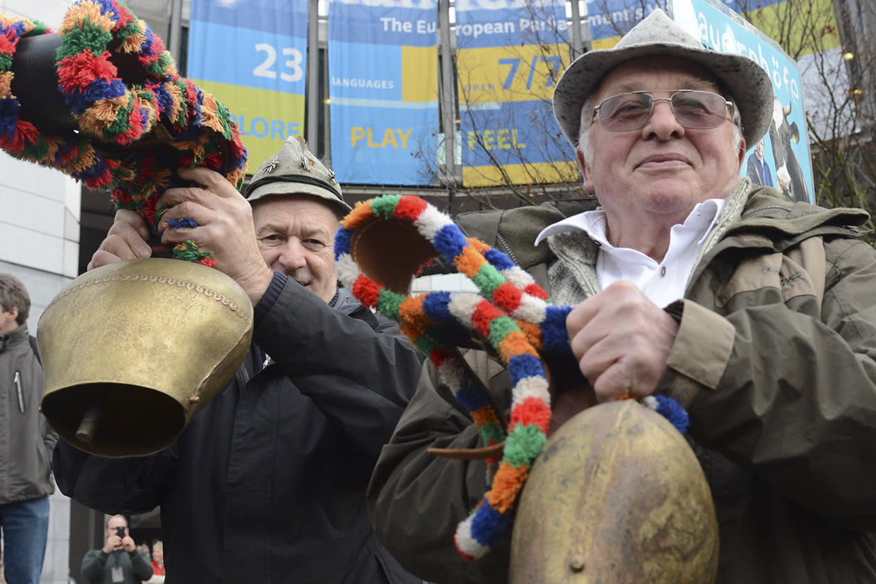 Two European milk farmers ring their cow bells in front of the European Parliament in Brussels.