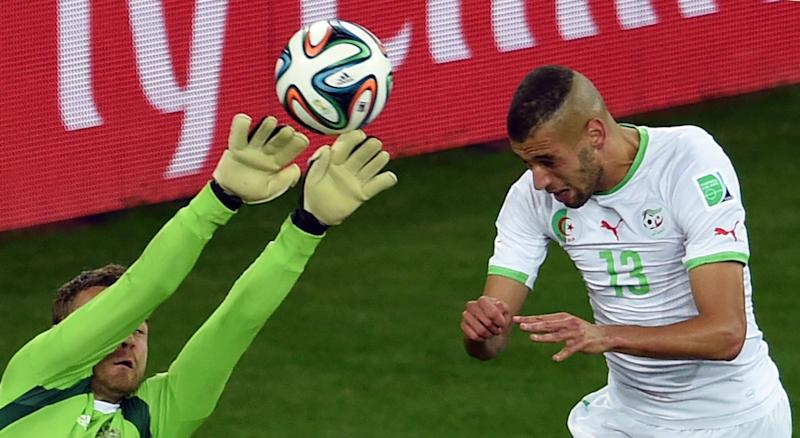 Algeria's forward Islam Slimani (R) heads the ball to score a goal past Russia's goalkeeper Igor Akinfeev during a World Cup match in Curitiba on June 26, 2014