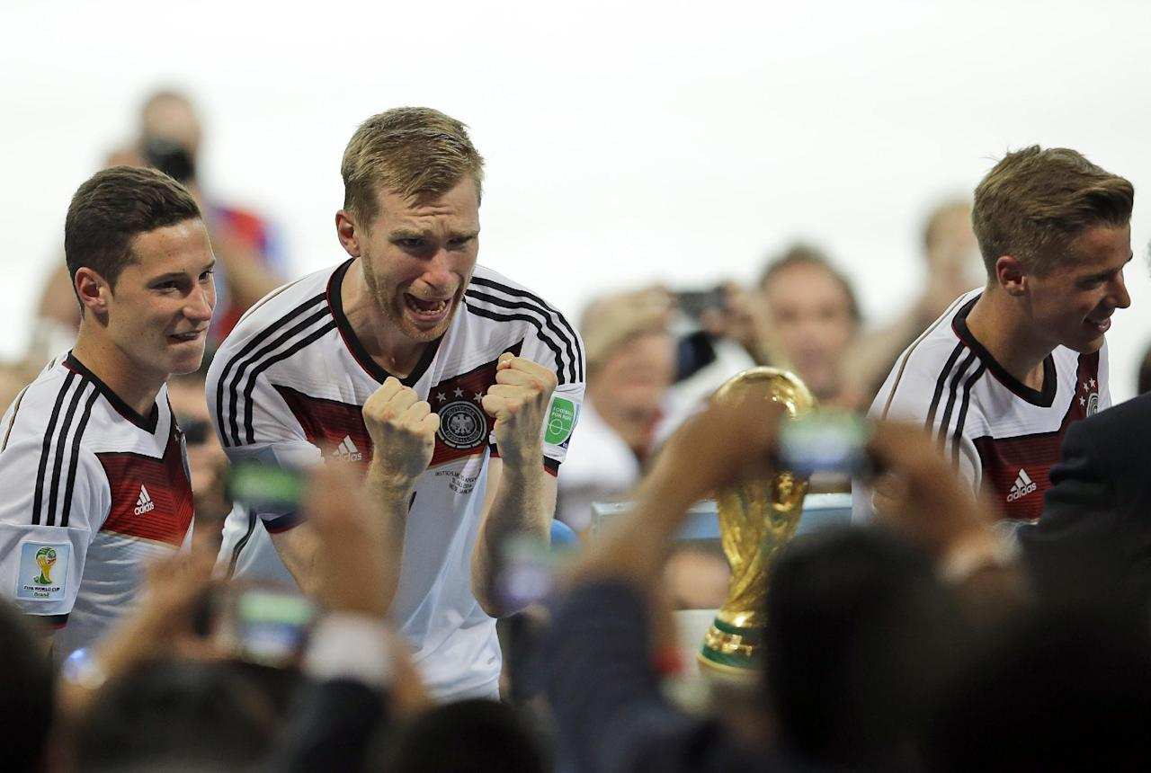 Germany's Per Mertesacker reacts as he looks at the World Cup trophy after the final match between Germany and Argentina at the Maracana Stadium in Rio de Janeiro, Brazil, Sunday, July 13, 2014. Germany won 1-0.(AP Photo/Hassan Ammar)