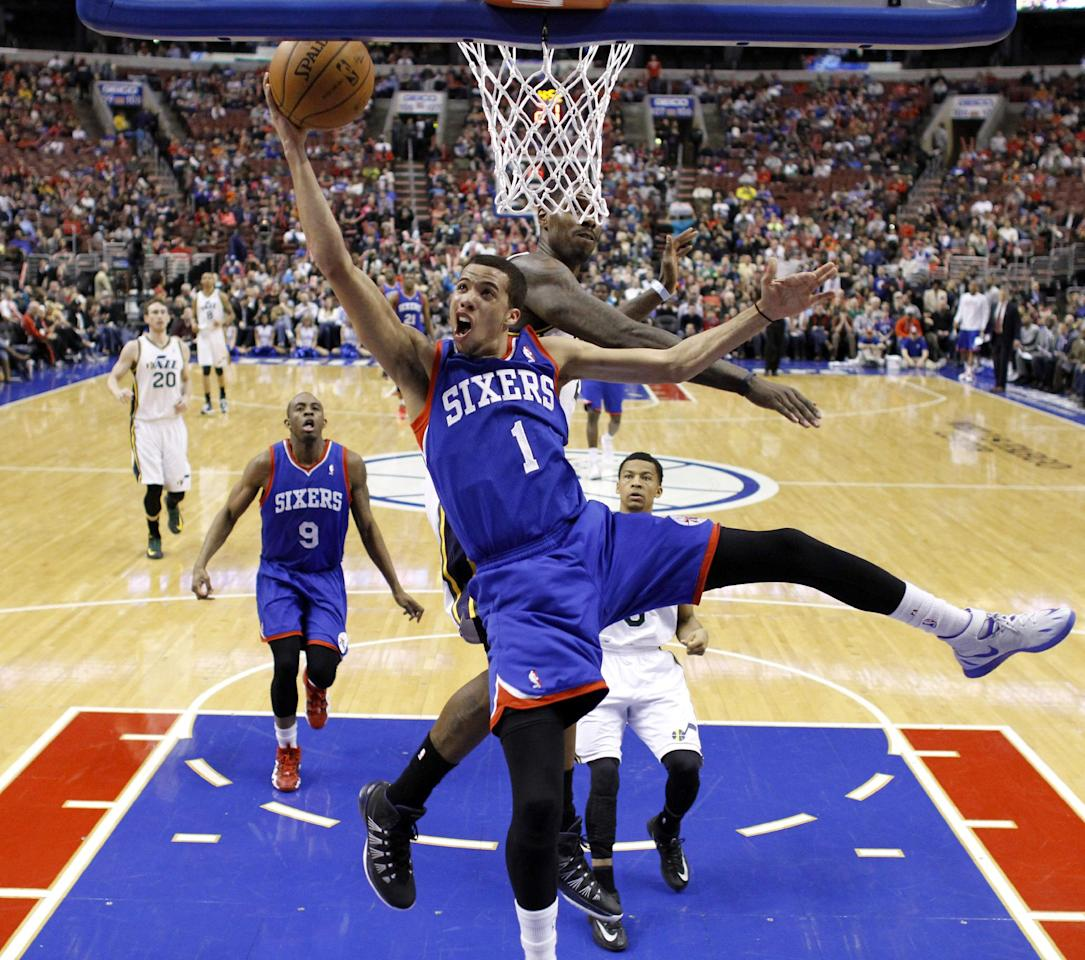 Philadelphia 76ers' Michael Carter-Williams (1) goes up to shoot against Utah Jazz's Marvin Williams during the first half of an NBA basketball game on Saturday, March 8, 2014, in Philadelphia. (AP Photo/Matt Slocum)