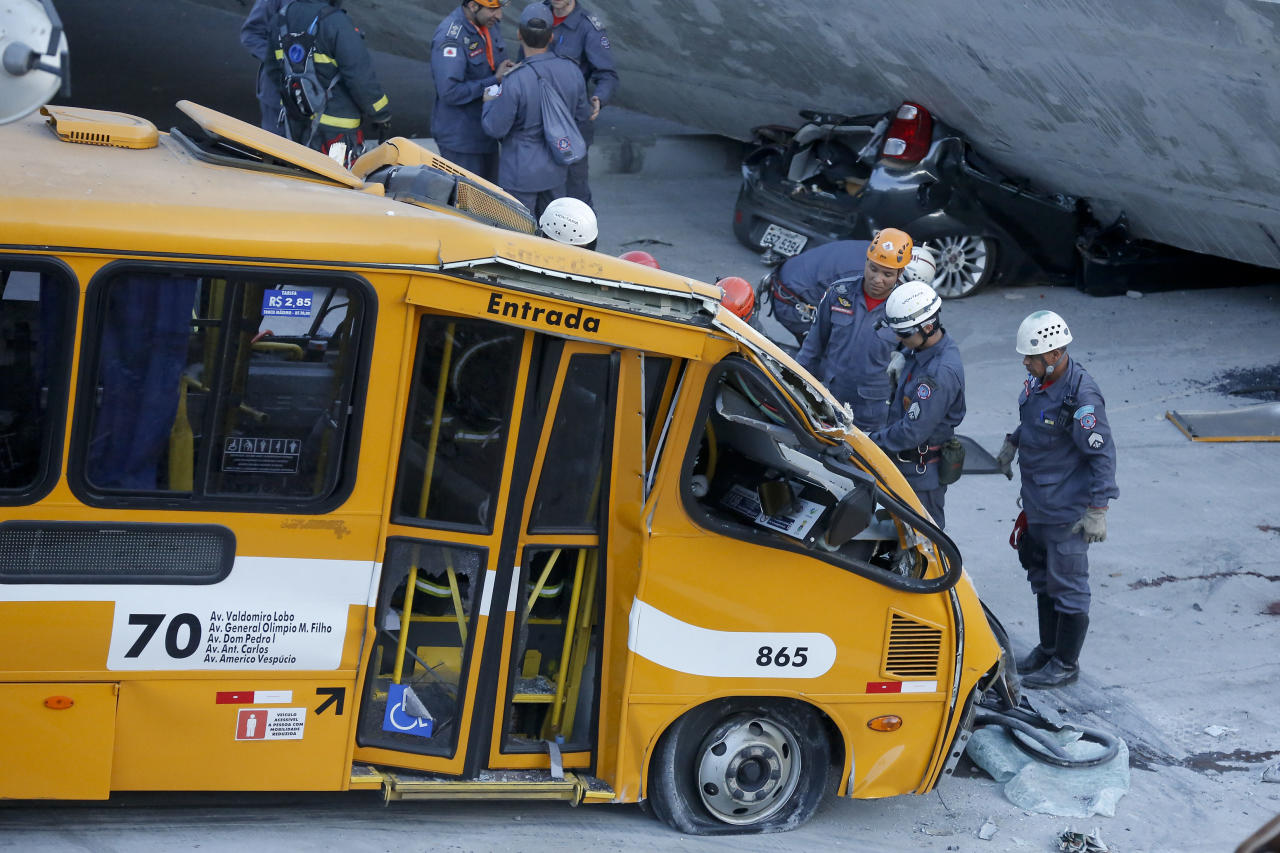 Fire department personnel work to retrieve a body from a bus after retrieving it from underneath a collapsed bridge in Belo Horizonte, Brazil, Thursday, July 3, 2014. The overpass under construction collapsed Thursday in the Brazilian World Cup host city. The incident took place on a main avenue, the expansion of which was part of the World Cup infrastructure plan but, like most urban mobility projects related to the Cup, was not finished on time for the event. (AP Photo/Victor R. Caivano)