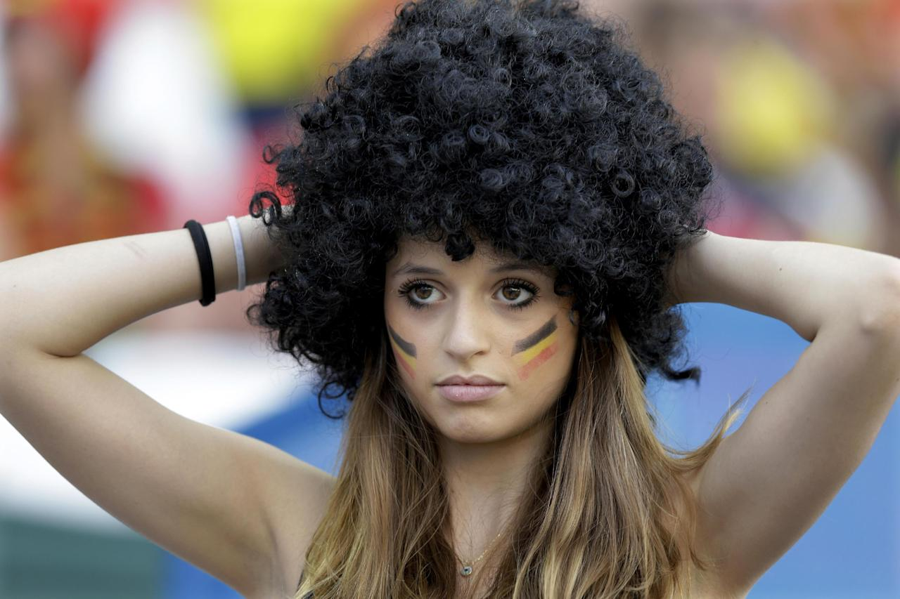 A Belgian supporter adjusts her wig before the group H World Cup soccer match between South Korea and Belgium at the Itaquerao Stadium in Sao Paulo, Brazil, Thursday, June 26, 2014. (AP Photo/Thanassis Stavrakis)