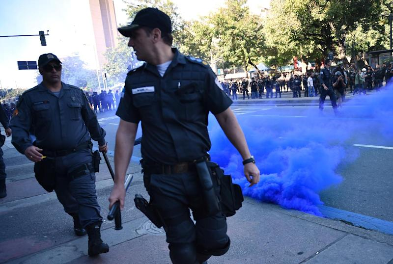 Police walk past a smoke bomb during a protest against the FIFA World Cup to demand better social services near the Maracana Stadium in Rio de Janeiro on July 13, 2014