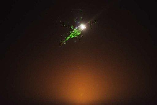 """Egyptian protestors direct lazer lights on a military helicopter flying over the presidential palace in Cairo, on July 1, 2013. Iran on Tuesday called on the Egyptian military to support national reconciliation and respect the """"vote of the people"""" after it warned it was ready to intervene in Egypt's political crisis"""