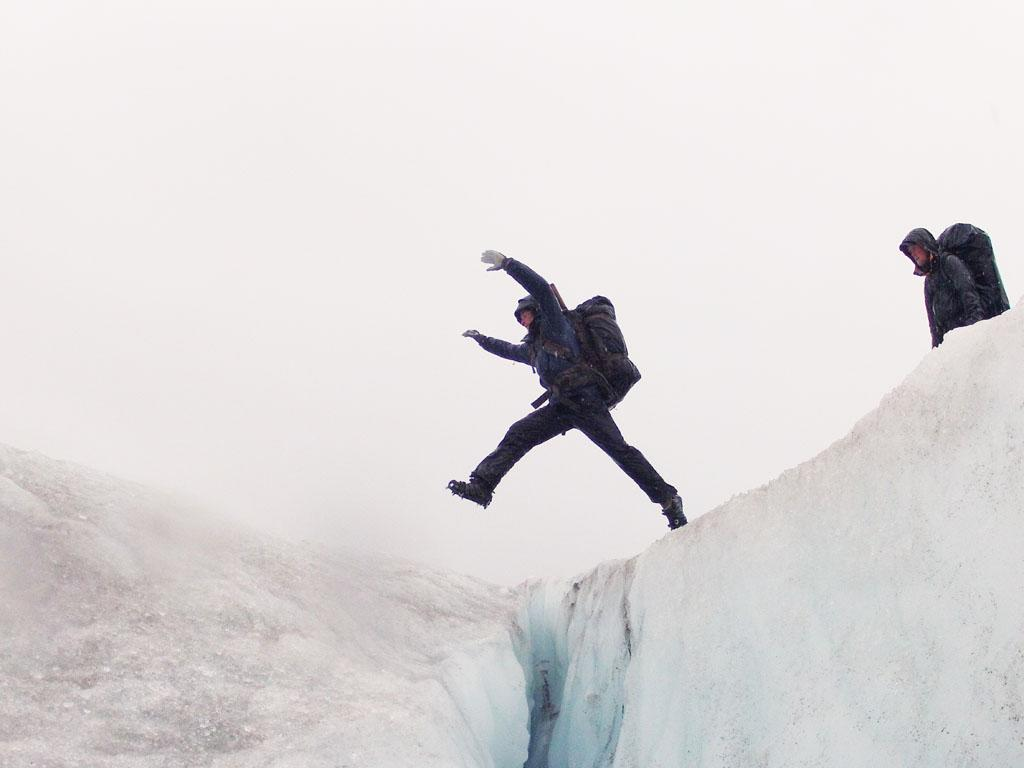 Tordrillo Mountains, Alaska, USA: Dallas Seavey leaping over crevasse.