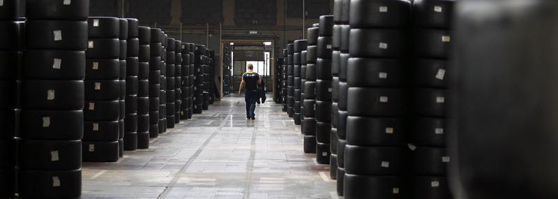 A worker walks past motorsport racing tyres stocked in the Michelin tyre company's factory in Clermont-Ferrand, central France