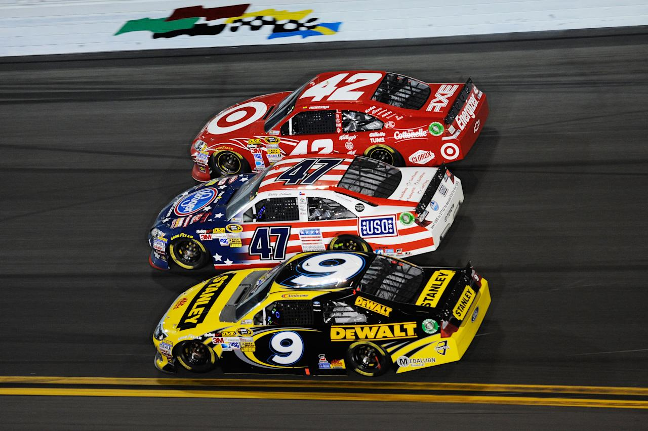 DAYTONA BEACH, FL - FEBRUARY 27:  Juan Pablo Montoya, driver of the #42 Target Chevrolet, Bobby Labonte, driver of the #47 Kroger Toyota, and Marcos Ambrose, driver of the #9 Stanley Ford, race three wide during the NASCAR Sprint Cup Series Daytona 500 at Daytona International Speedway on February 27, 2012 in Daytona Beach, Florida.  (Photo by John Harrelson/Getty Images for NASCAR)