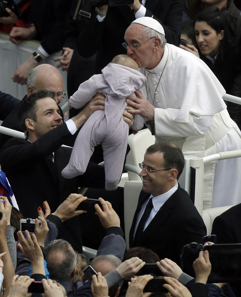 Pope Francis kisses a baby after celebrating his first Easter Mass in St. Peter's Square at the Vatican, Sunday, March 31, 2013. Pope Francis celebrated his first Easter Sunday Mass as pontiff in St. Peter's Square, packed by joyous pilgrims, tourists and Romans and bedecked by spring flowers. Wearing cream-colored vestments, Francis strode onto the esplanade in front of St. Peter's Basilica and took his place at an altar set up under a white canopy. (AP Photo/Gregorio Borgia)