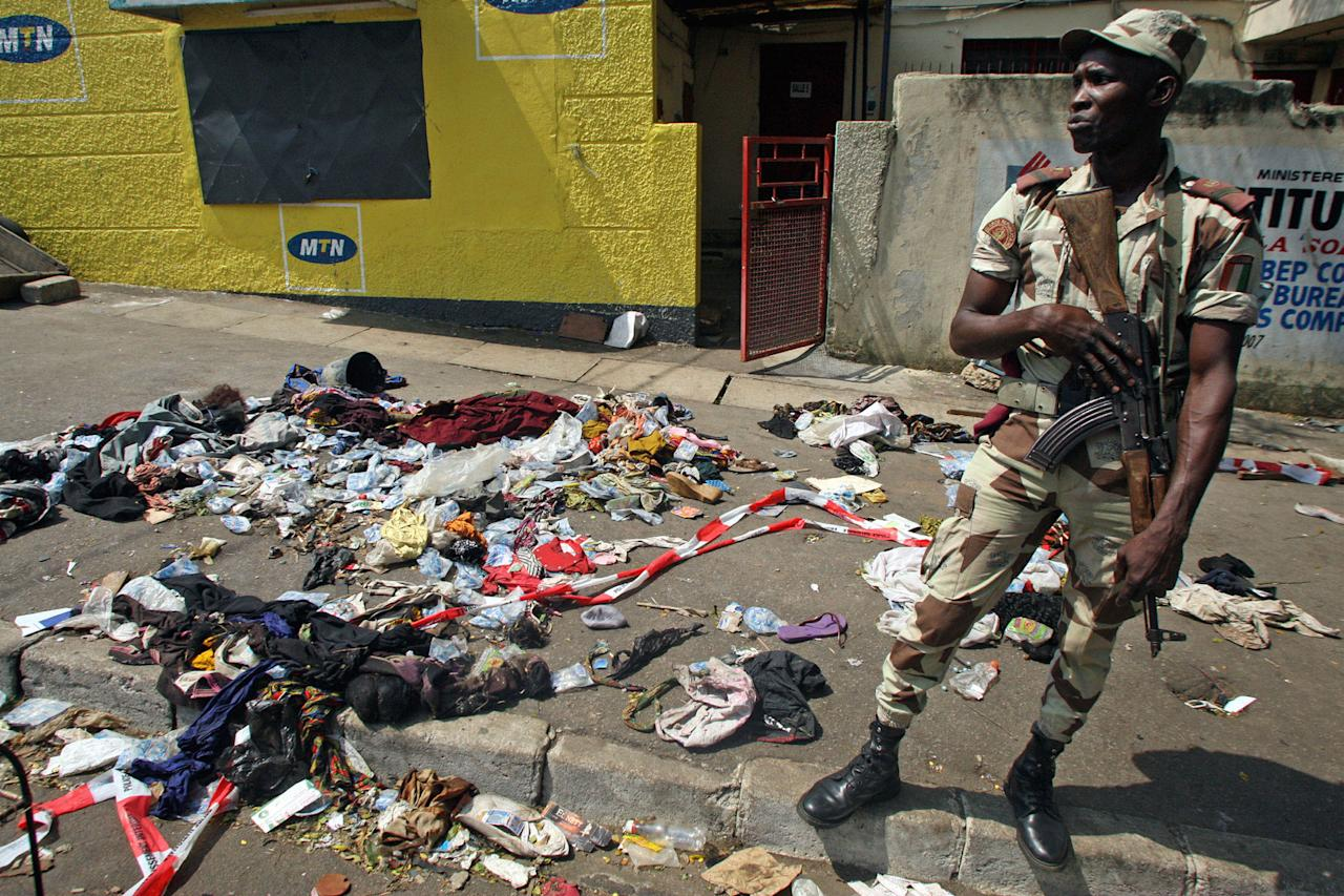 An Ivory Coast troop stands next to the belongings of people involved in a deadly stampede in Abidjan, Ivory Coast, Tuesday, Jan. 1 2013. At least 61 people were killed early Tuesday in a stampede following a New Year's fireworks display in Abidjan, Ivory Coast's commercial center, said officials. The death toll is expected to rise, according to rescue workers. (AP Photo/Emanuel Ekra)