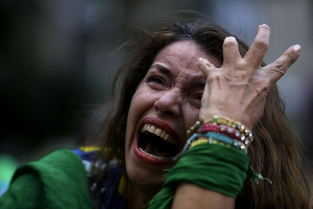 A Brazilian soccer fan cries as she watches her team during a live telecast of the semifinals World Cup soccer match between Brazil and Germany, in Belo Horizonte, Brazil, Tuesday, July 08, 2014. (AP Photo/Bruno Magalhaes)