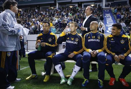 Los Angeles Galaxy midfielder Rogers sits on his team bench in front of head coach Arena before their MLS soccer game against the Seattle Sounders in Carson