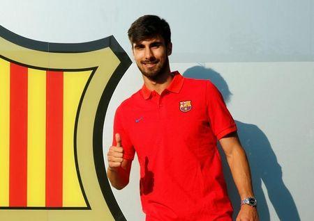 Soccer player Andre Gomes poses next to a FC Barcelona's giant logo at their offices in Barcelona, Spain, July 26, 2016.  REUTERS/Albert Gea