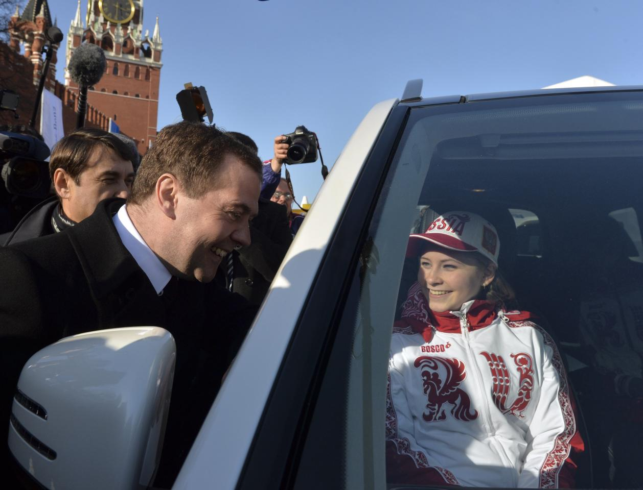 Russia's Prime Minister Dmitry Medvedev and figure skating gold medal winner Yulia Lipnitskaya (R) attend a ceremony to present automobiles to the Sochi 2014 Winter Olympics prize-holders representing Russia, by the Kremlin wall in central Moscow, February 27, 2014. REUTERS/Artem Zhitenev/RIA Novosti/Pool (RUSSIA - Tags: POLITICS SPORT OLYMPICS) ATTENTION EDITORS - THIS IMAGE HAS BEEN SUPPLIED BY A THIRD PARTY. IT IS DISTRIBUTED, EXACTLY AS RECEIVED BY REUTERS, AS A SERVICE TO CLIENTS