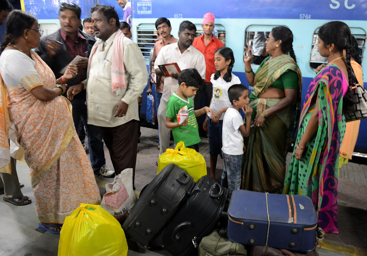 Indian pilgrims, who were stranded in the Kedarnath region of northern Uttarkhand due to heavy rains and landslides, gesture on arrival at the railway station in Secunderabad, the twin city of Hyderabad on June 25, 2013. Indian officials stepped up efforts on June 25 to prevent an outbreak of disease in the northern Himalayan region devastated by landslides and flash floods, as rains hampered the rescue of thousands still stranded.     AFP PHOTO / Noah SEELAM
