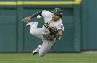 A's outfielder Coco Crisp bobbles a hit in the seventh inning of Game 2. (AP)