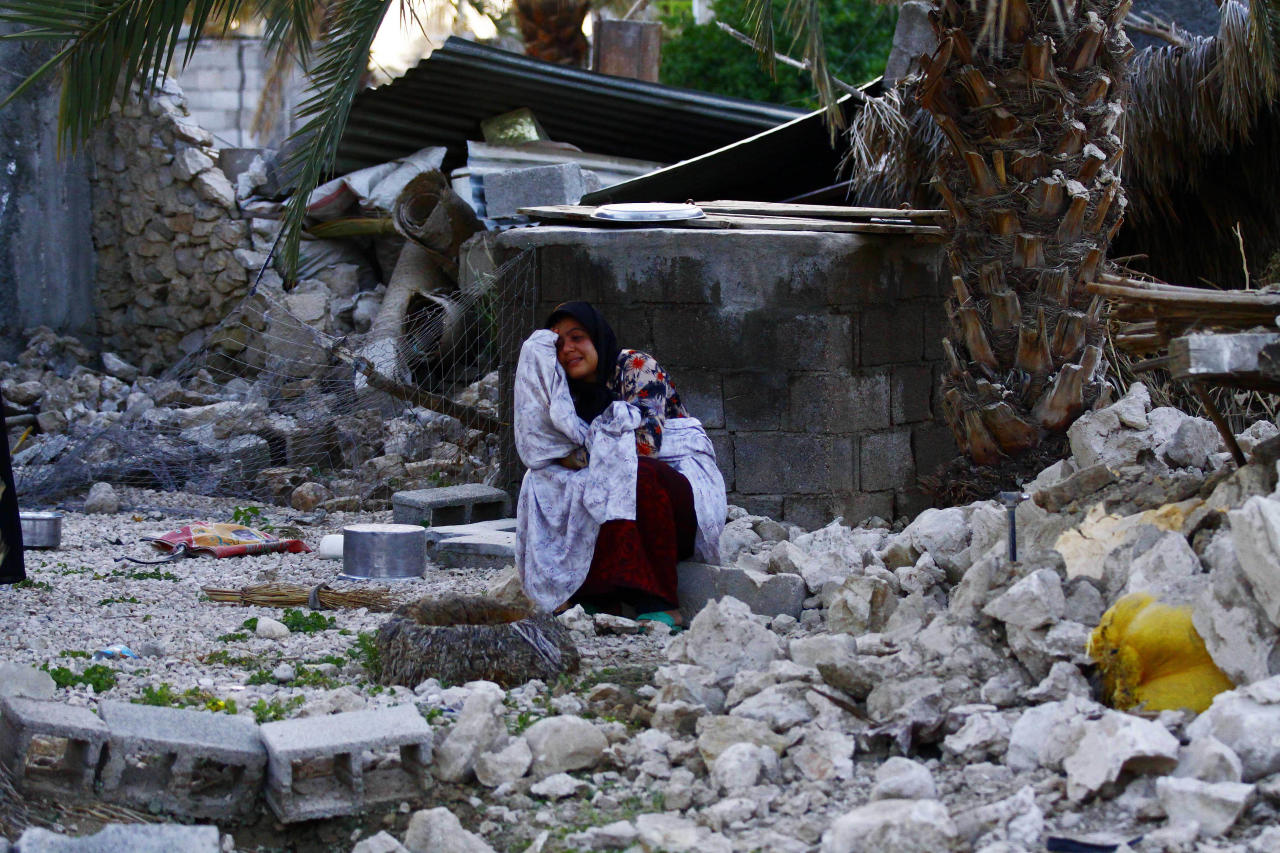 An Iranian woman reacts as she sits among the rubble of buildings after an earthquake struck southern Iran, in Shonbeh, Iran, Tuesday, April 9, 2013. A 6.1 magnitude earthquake killed dozens of people and injured hundreds more in a sparsely populated area in southern Iran on Tuesday, Iranian officials said, adding that it did not damage a nuclear plant in the region. (AP Photo/Fars News Agency, Mohammad Fatemi)