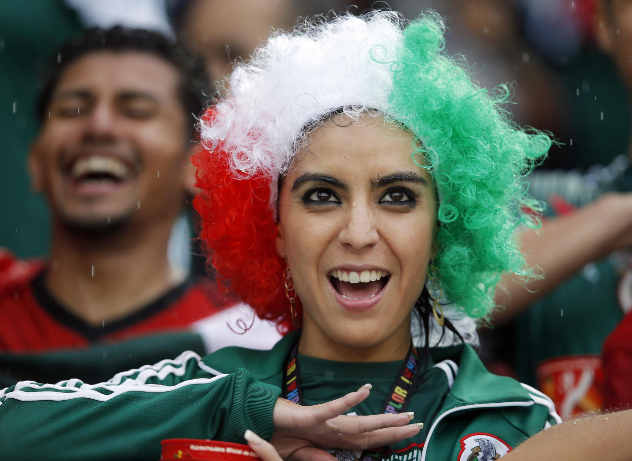 A Mexican fan sings her country's national anthem before the group A World Cup soccer match between Mexico and Cameroon in the Arena das Dunas in Natal, Brazil, Friday, June 13, 2014. (AP Photo/Eduardo Verdugo)
