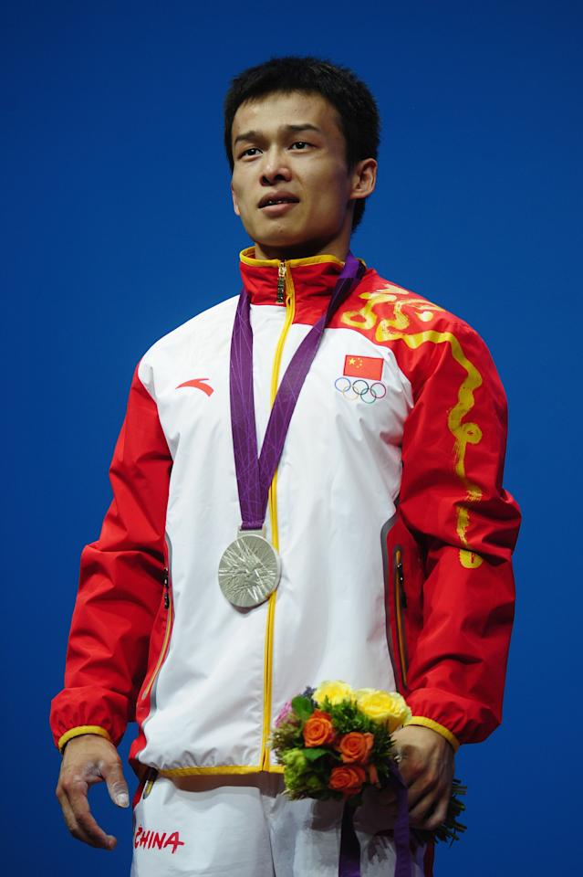 LONDON, ENGLAND - JULY 29:  Jingbiao Wu of China celebrates with the silver medal on the podium after the Men's 56kg Weightlifting on Day 2 of the London 2012 Olympic Games at ExCeL on July 29, 2012 in London, England.  (Photo by Laurence Griffiths/Getty Images)