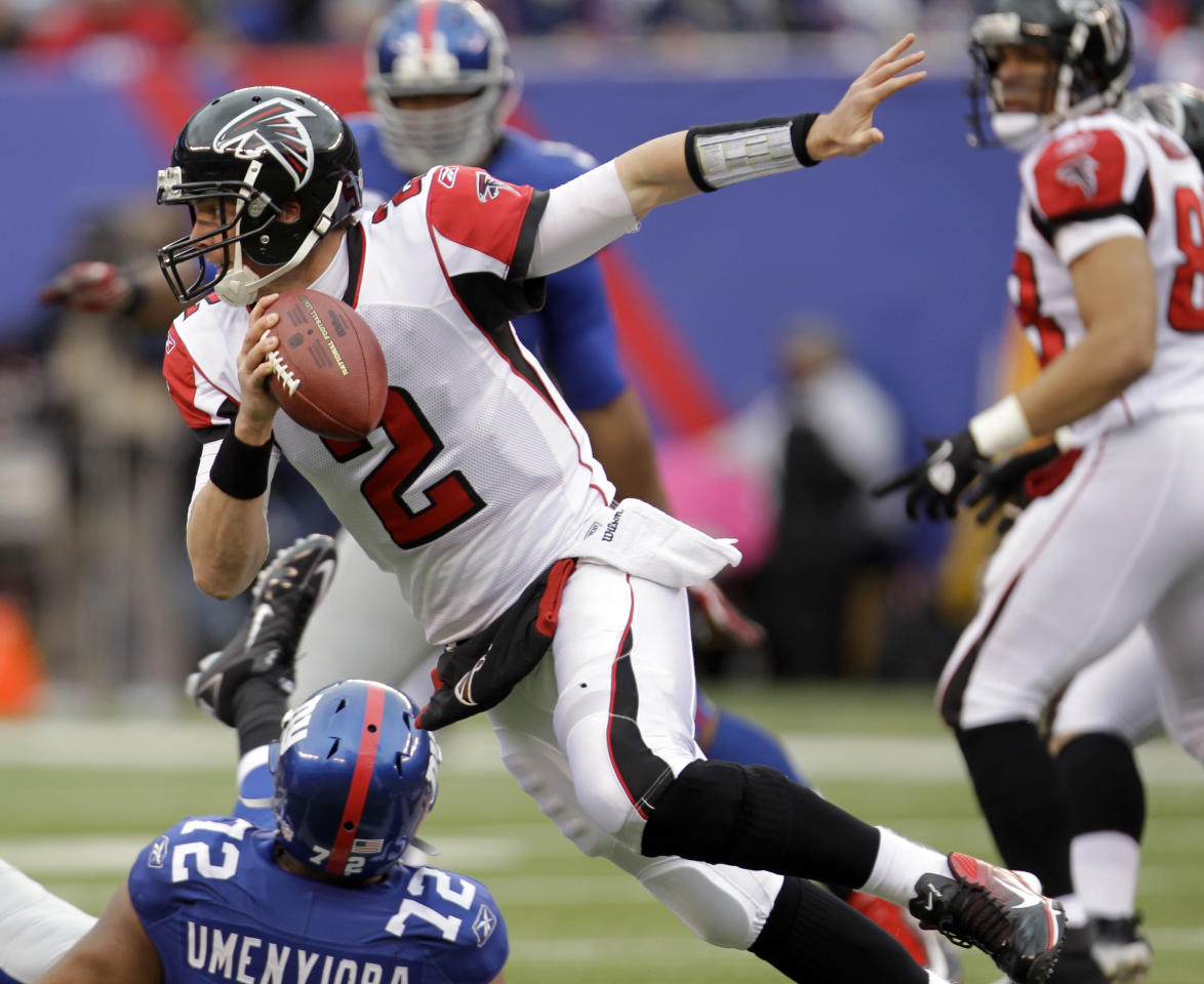 Atlanta Falcons quarterback Matt Ryan (2) runs over New York Giants defensive end Osi Umenyiora (72) during the first half of an NFL wild card playoff football game Sunday, Jan. 8, 2012, in East Rutherford, N.J. (AP Photo/Julio Cortez)