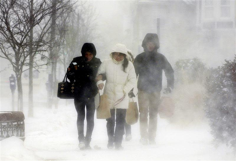 Elmwood Village residents walk down Elmwood Avenue after purchasing needed items from a grocery store in Buffalo