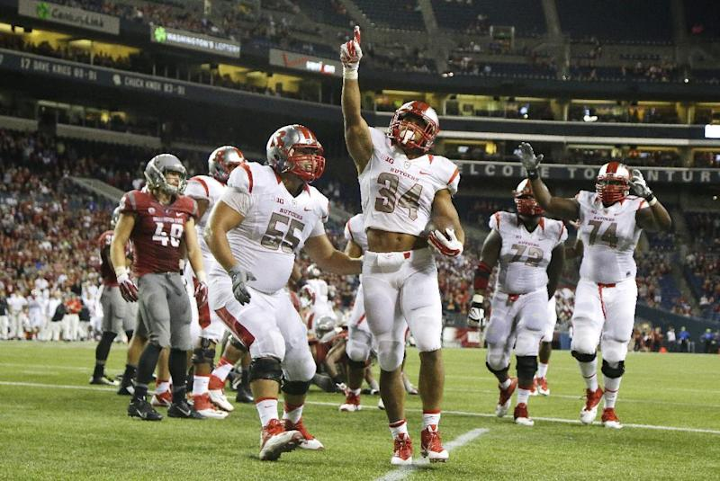 Rutgers running back Paul James (34) points upward after he rushed for a touchdown in the second half of an NCAA college football game against Washington State, Thursday, Aug. 28, 2014, in Seattle. Rutgers beat Washington State 41-38