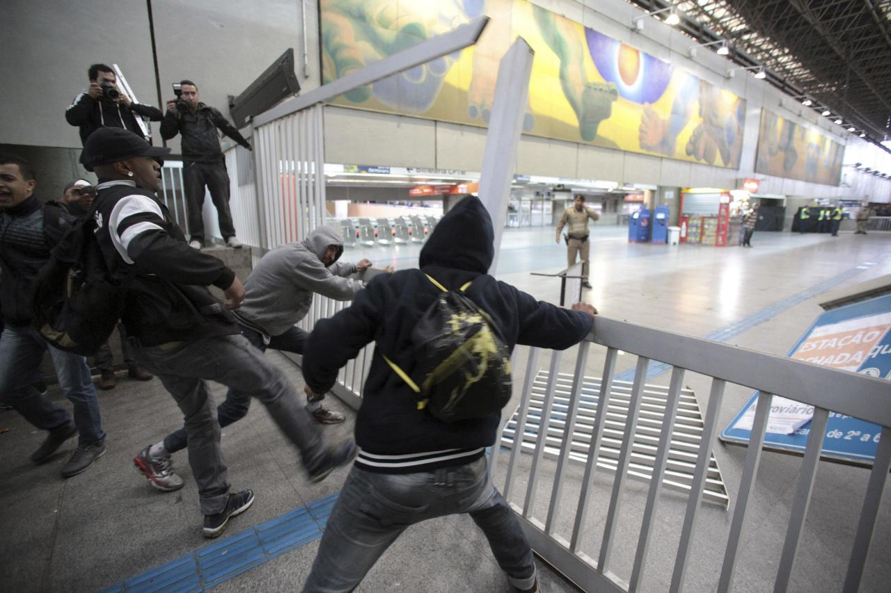 Commuters break an entrance gate at Itaquera subway station in Sao Paulo June 5, 2014. Union workers of Sao Paulo's Metro subway system are on strike since midnight, with just a week to go before the 2014 World Cup opens in Brazil, local media reported. REUTERS/Chico Ferreira (BRAZIL - Tags: SPORT SOCCER WORLD CUP CIVIL UNREST POLITICS TRANSPORT)
